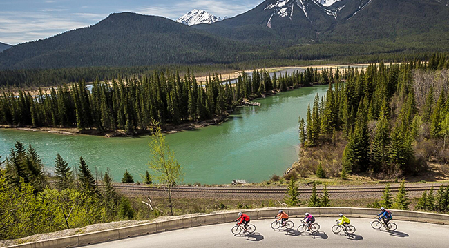 Bikers, river and mountains on route from Jasper to Banff on a guided cycling tour in Canadian Rocky Mountains