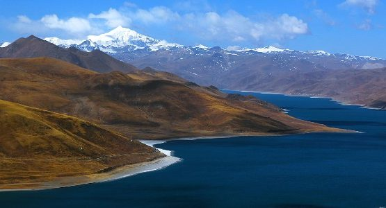 A lakeshore in Tibet with mountains in the distance
