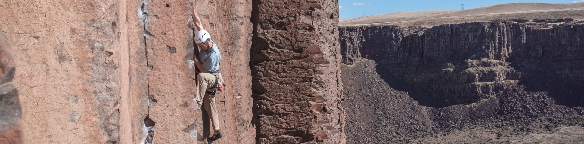 Climber ascending on a steep rock wall in a valley