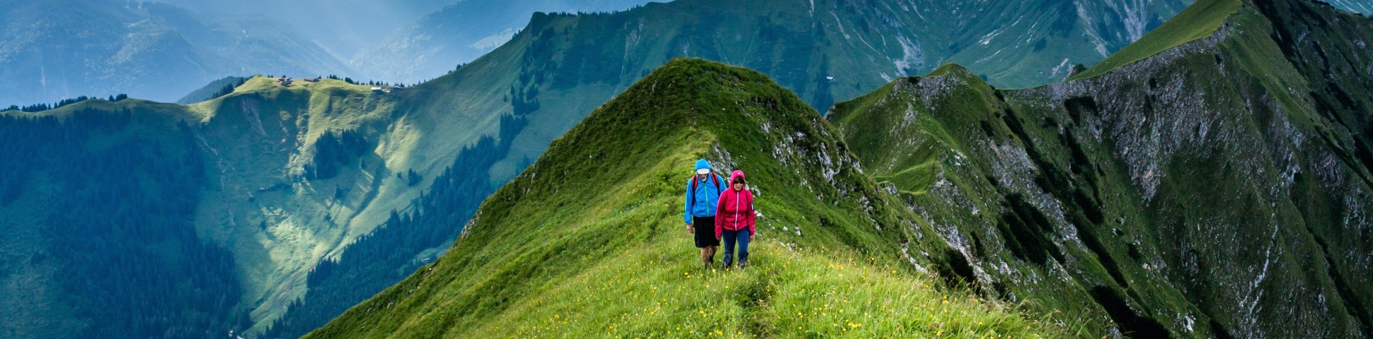Two hikers walking on a ridge among the green mountains