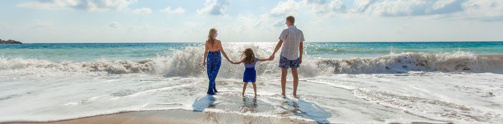 Family walking along the beach while on a guided tour