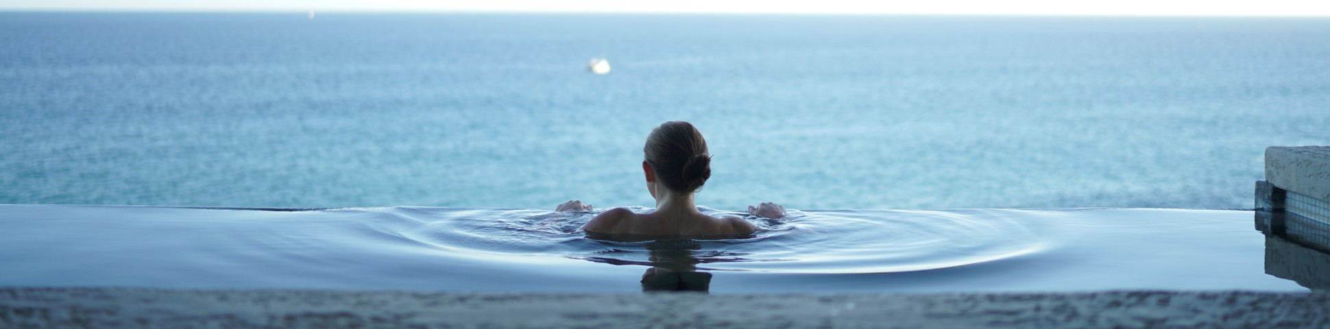 Lady in a swimming pool with an ocean behind, Wellness Tours