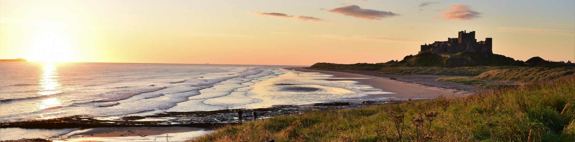 castle in northumberland on the coast with two people on the beach below