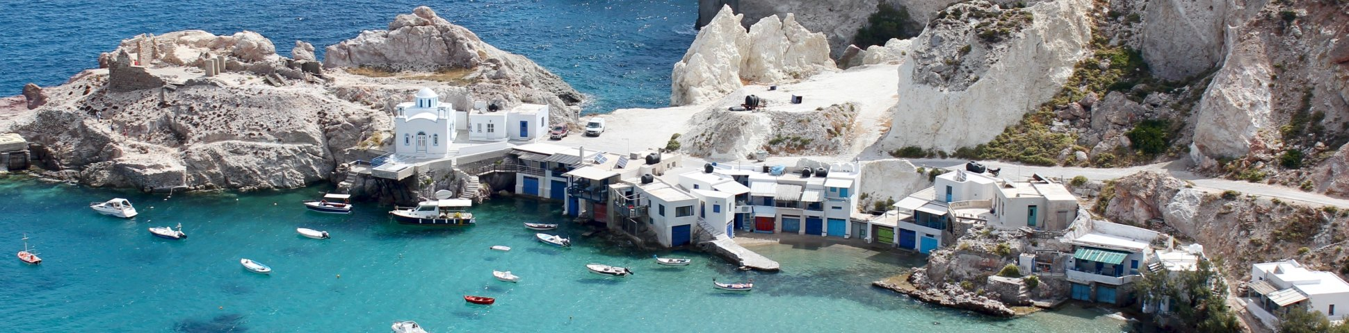 White buildings and jagged rocks on the coast of a Cyclades island surrounded by blue water with boats