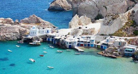 White buildings and jagged rocks on the coast of a Cyclades island surrounded by blue water with boats (1)
