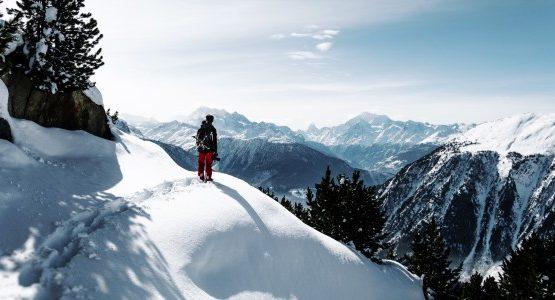 Hiker walking among snowed in mountains