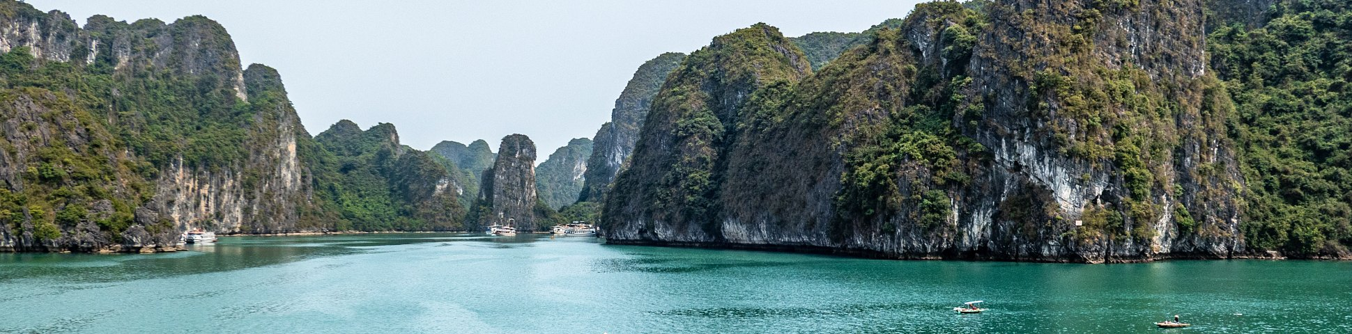 Wide-angle shot of Ha Long Bay in Vietnam, with blue ocean and tree-covered hills