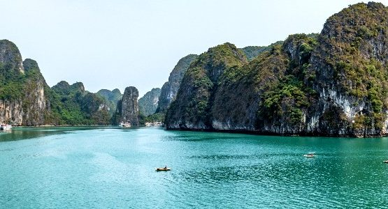 Ocean and hills of Ha Long Bay with a person in a kayak on the water