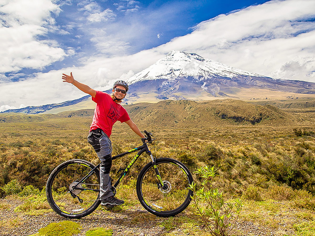 Biker in front of Cotopaxi on Cross Country Cycling in Ecuadorian Andes