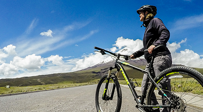 Biker near Cotopaxi Volcano on cross country biking tour in Ecuador