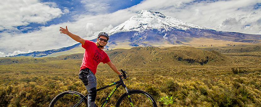 Man enjoying the bike ride and Cotopaxi Volcano views on cross country cycling tour in Ecuador with group