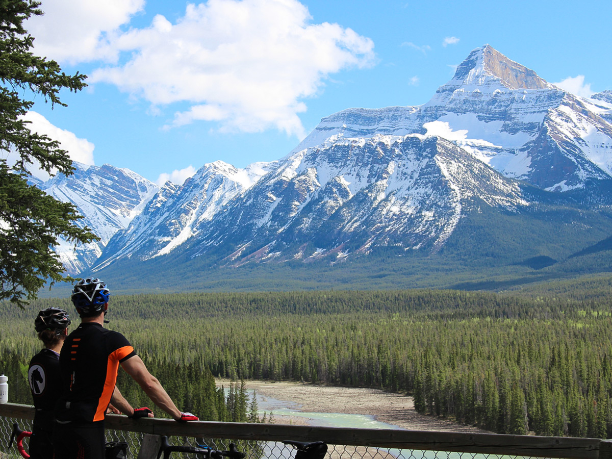 Two bikers looking at Canadian Rockies on guided cycling tour from Jasper to Banff in Canada