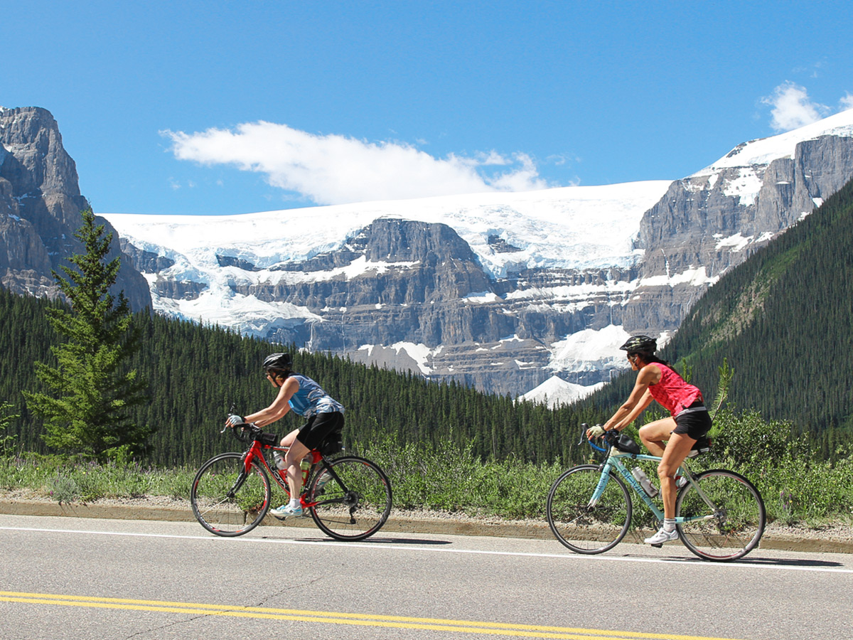 Two women biking in front of beautiful glaciers on guided cycling tour from Jasper to Banff in Canada