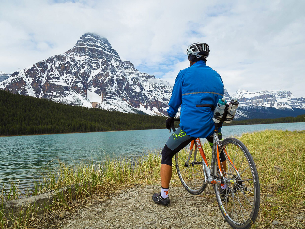 Biker looking at beautiful lake on guided cycling tour from Jasper to Banff in Canada