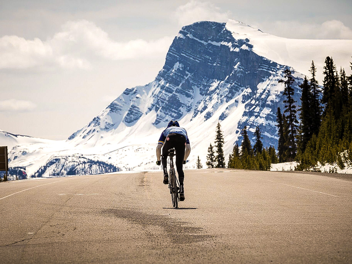 Approaching the snowy mountains on guided cycling tour from Jasper to Banff in Canada