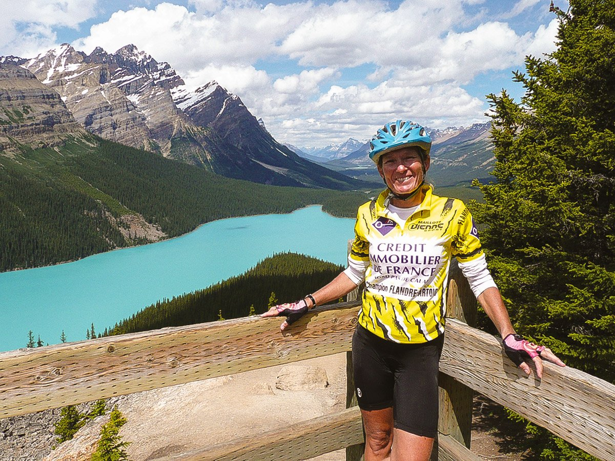 Biker posing near turquoise lake on guided cycling tour from Jasper to Banff in Canada