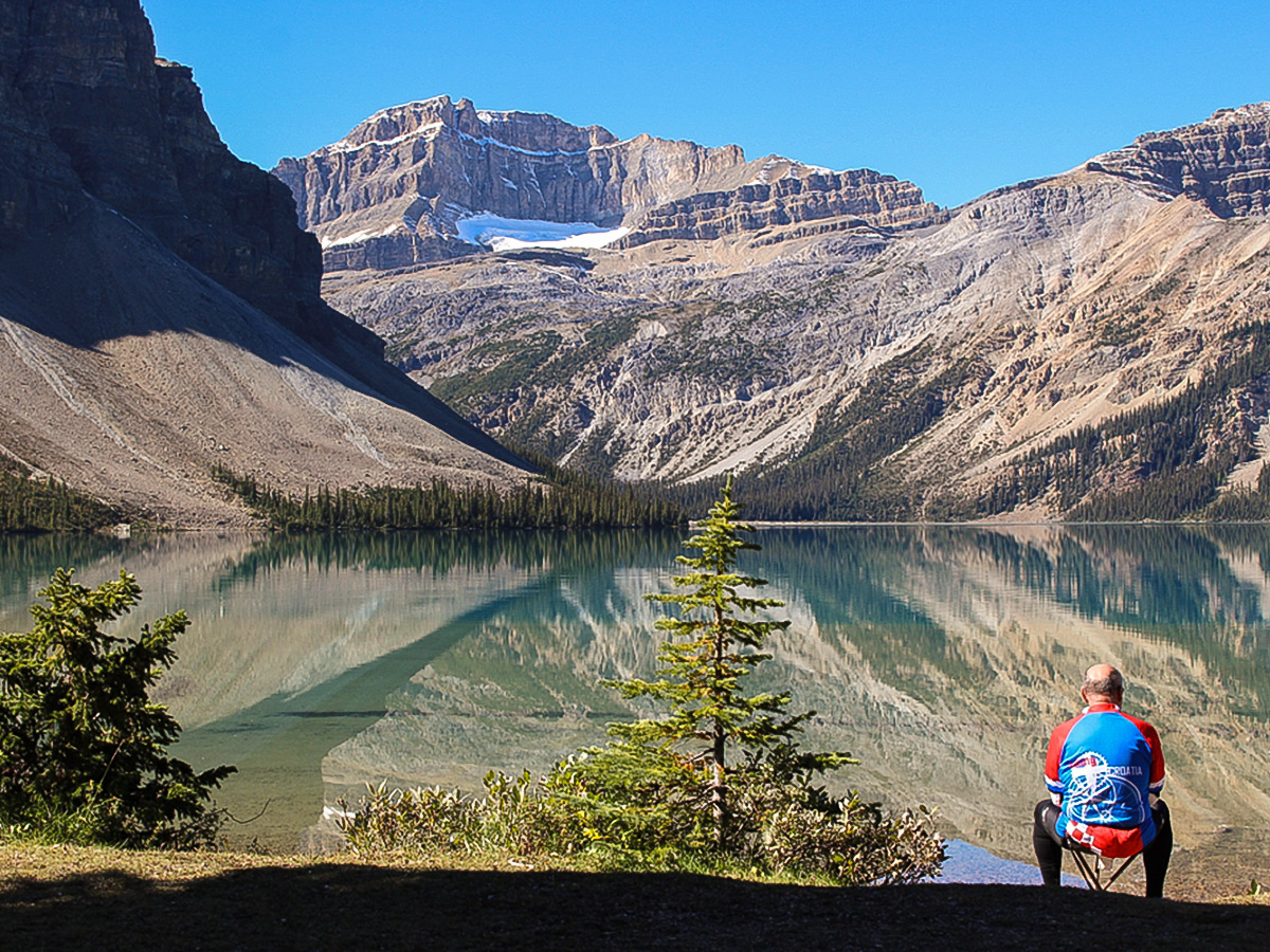 Biker resting near beautiful lake on guided cycling tour from Jasper to Banff in Canada