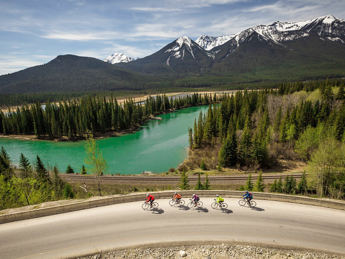 Bikers riding on Icefields Parkway surrounded by beautiful views on guided cycling tour from Jasper to Banff in Canada