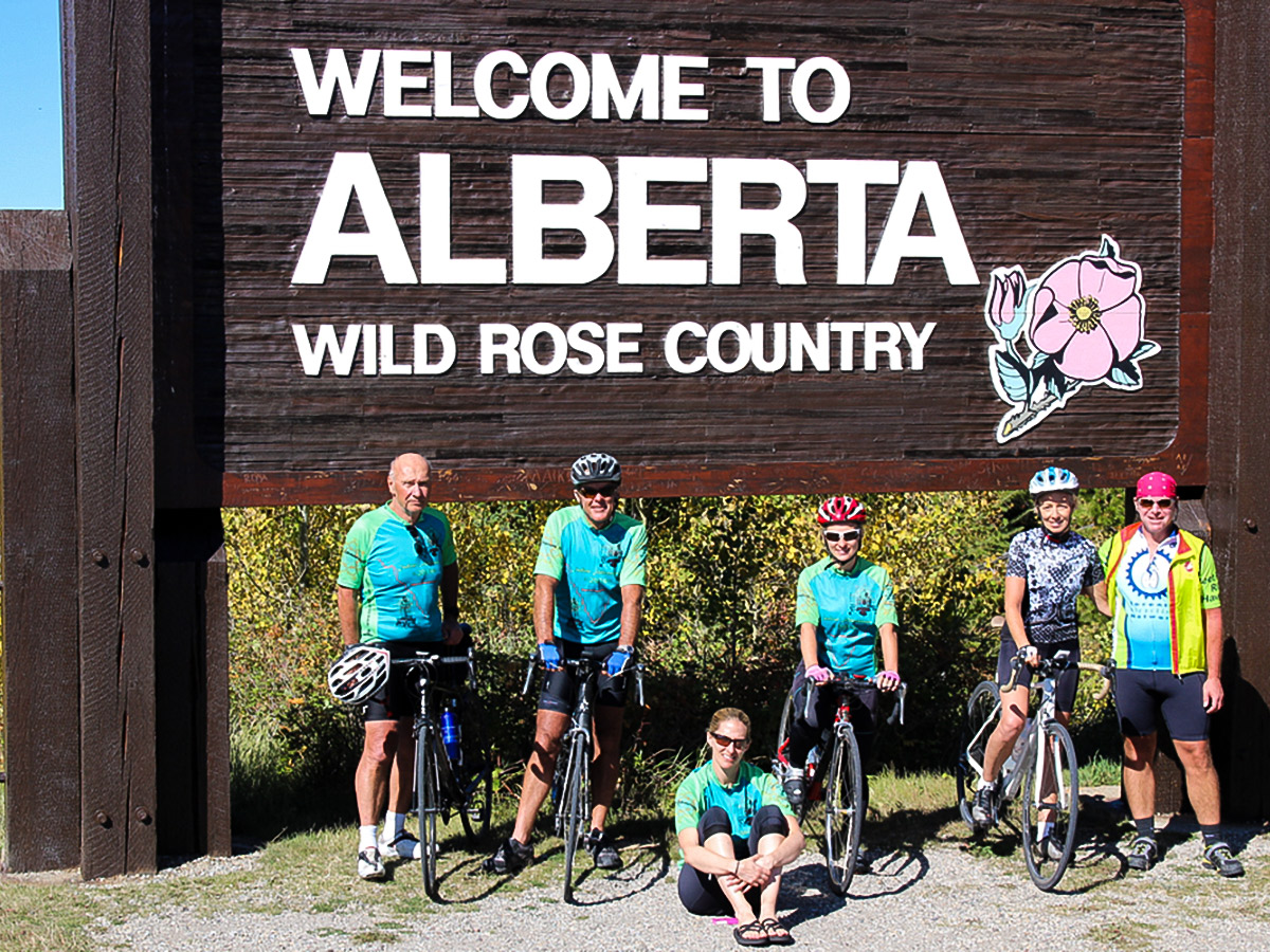 Bikers near Alberta sign on guided cycling tour from Jasper to Banff in Canada