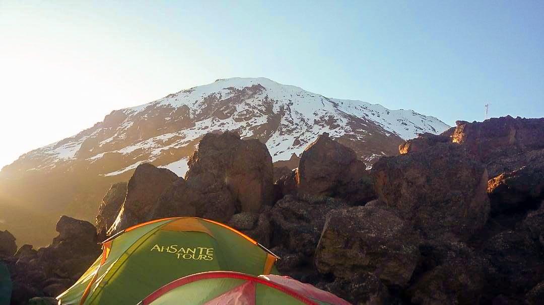 Mount Kilimanjaro above the tents on Kilimanjaro trek on Machame Route in Tanzania