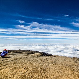 Hiker above the clouds on Kilimanjaro trek on Lemosho Route in Tanzania