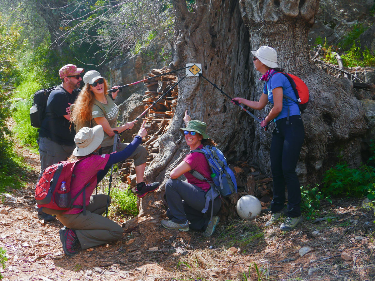 Happy hikers near the sign on guided trek in the White Mountains of Crete, Greece