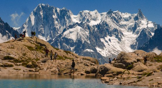 Group of hikers near the lake on Tour de Mont Blanc in French Alps