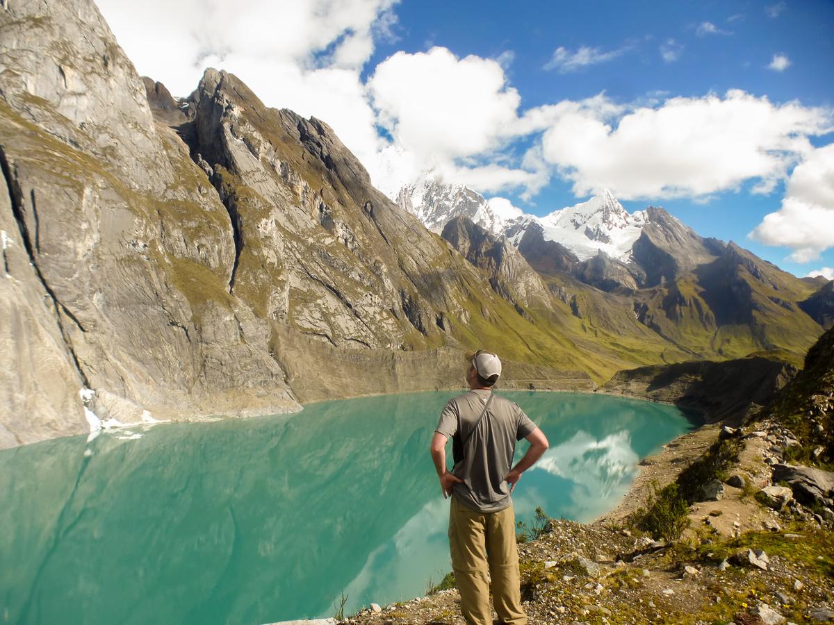 Hiker and turquoise lake on standart Huayhuash circuit trek, Peru