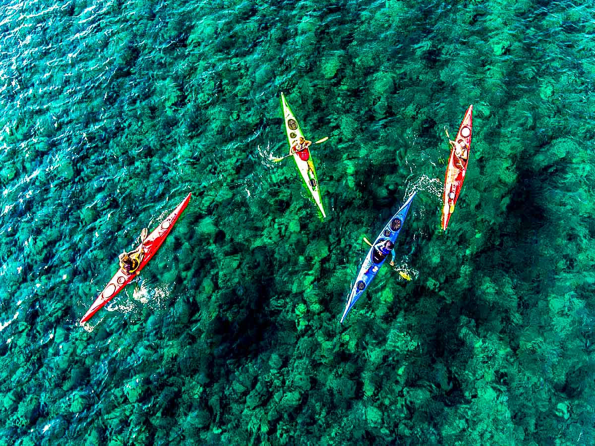 Four kayakers on beautiful water on Greek Islands Multisport tour
