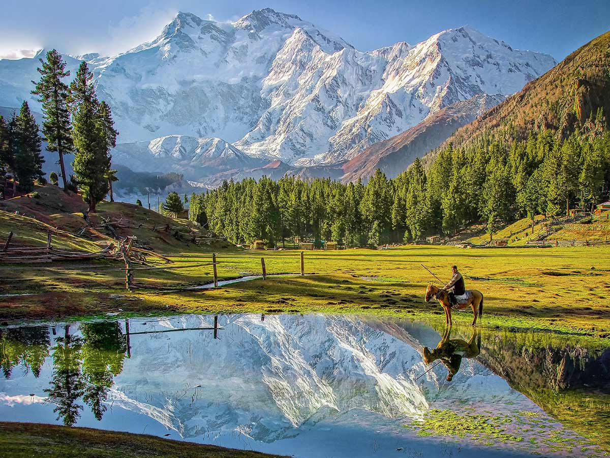 Beautiful mountains, lake and man on a horse on Fairy Meadows and Nanga Parbat Base Camp Tour in Pakistan