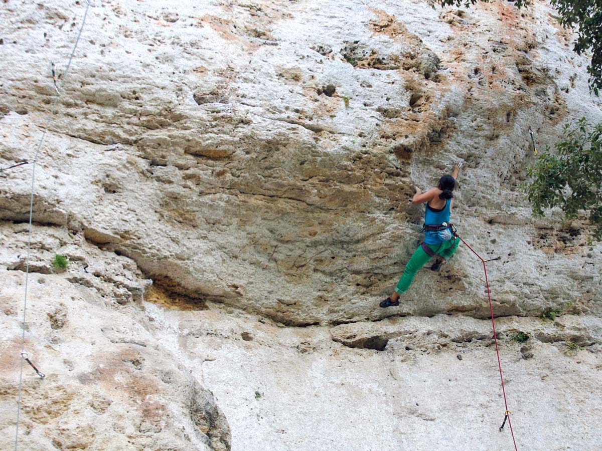 Woman climbing up on rock climbing tour in Finale Ligure