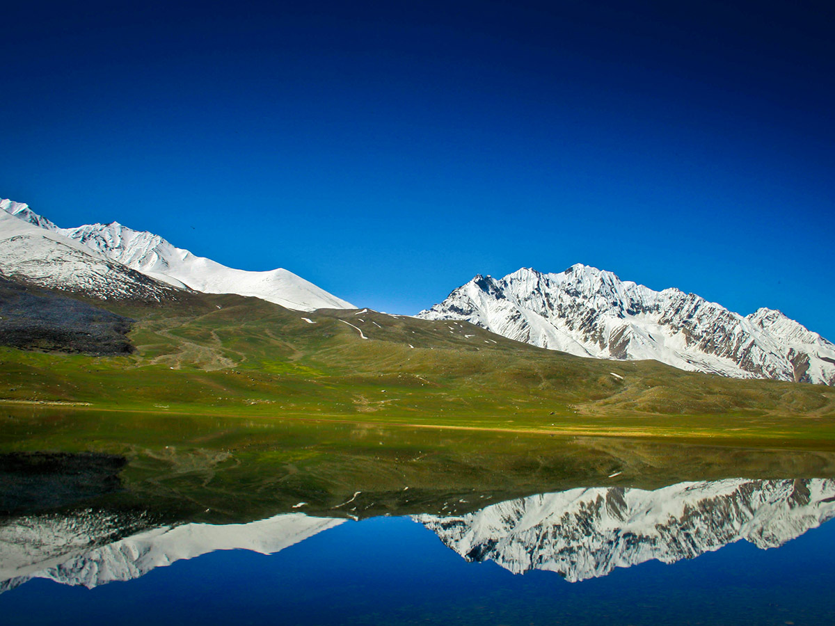 Reflections on Shandur Lake on Chitral Valley Overland Tour in Pakistan