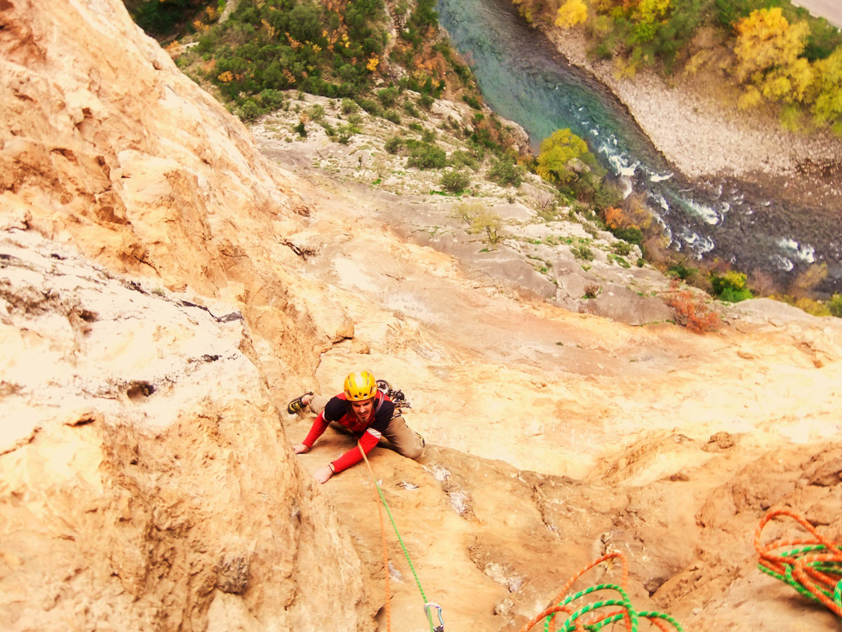 Climbing on rock above the river in Aragon on Trad and Multipitch rock climbing tour in Riglos, Spain