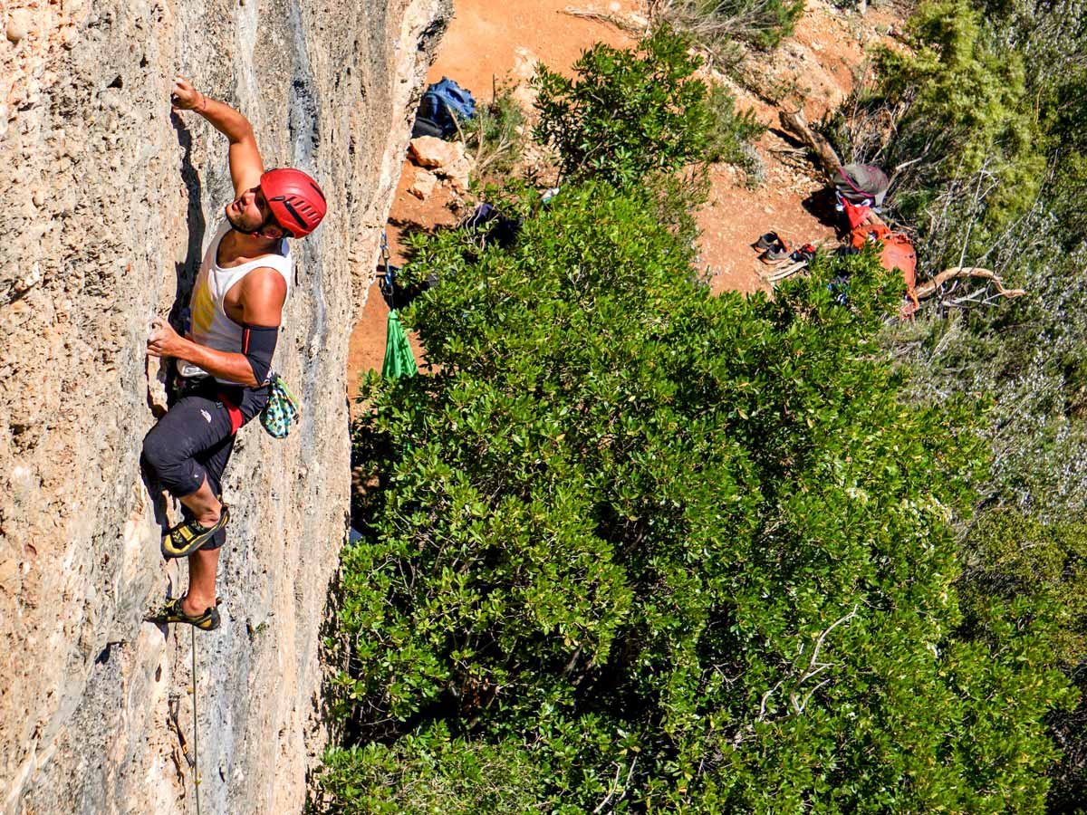 Climber on vertical rock wall on rock climbing tour in Margalef, Spain