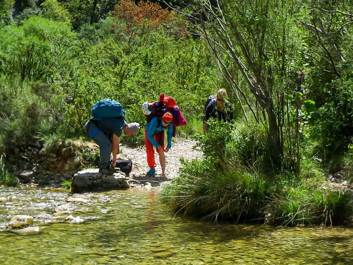 Three rock climbers about to cross a stream near Rodellar