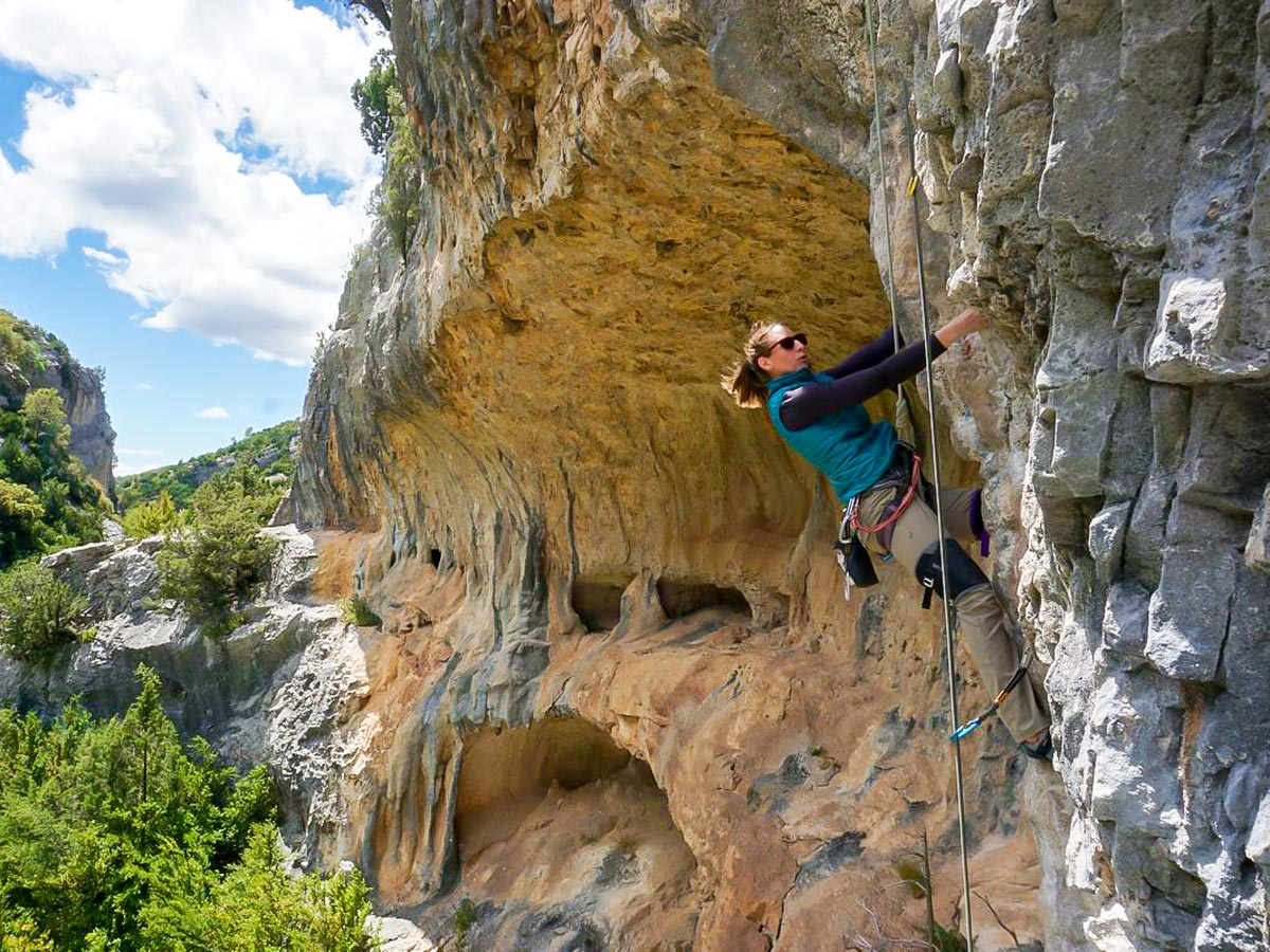 Woman climbing on beautiful rock formations in Spain on women's climbing camp