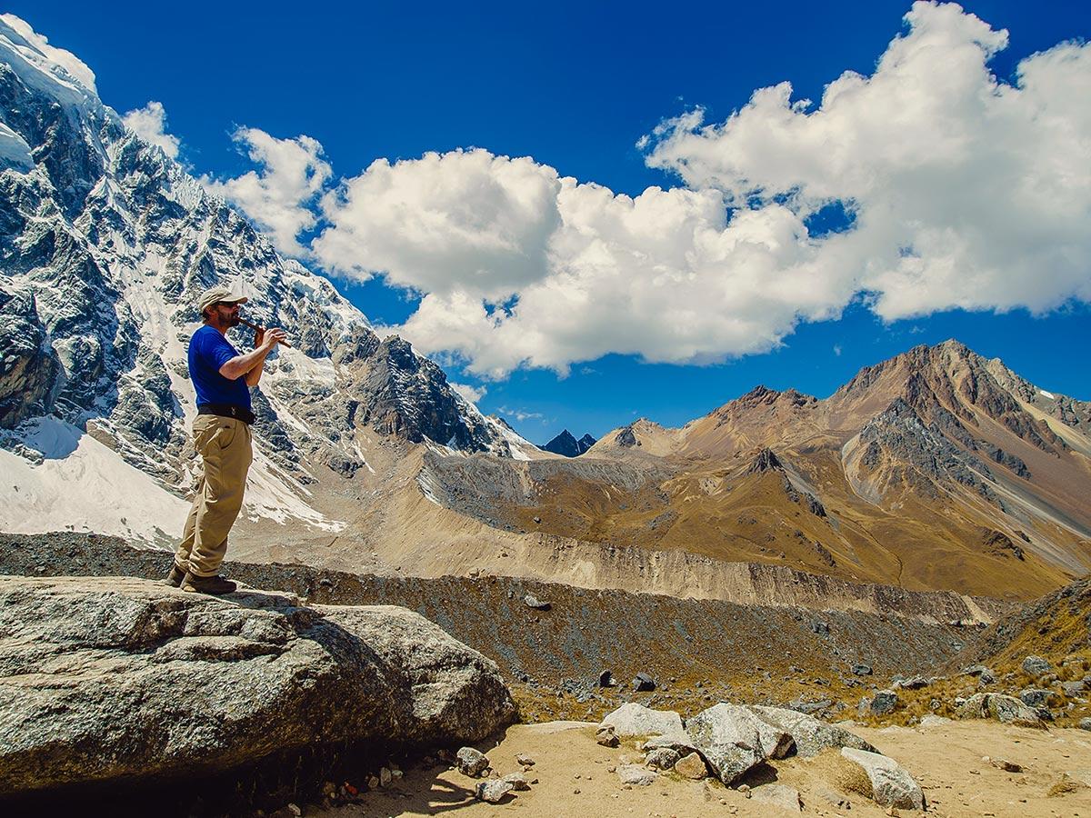 Hiker playing flute on Salkantay Trek to Machu Picchu in Peru