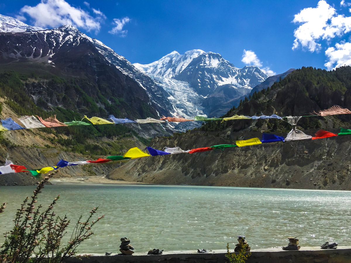 Prayer flags in front of the river on guided Annapurna Circuit hike in Nepal