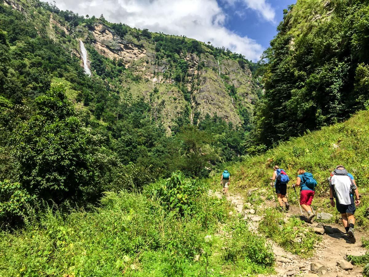 Group of hikers and waterfall on Manaslu Circuit trek in Nepal