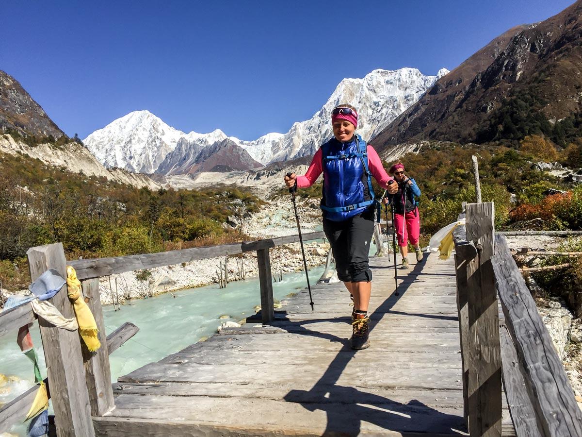 Happy hikers crossing the river on Manaslu Circuit trek in Nepal