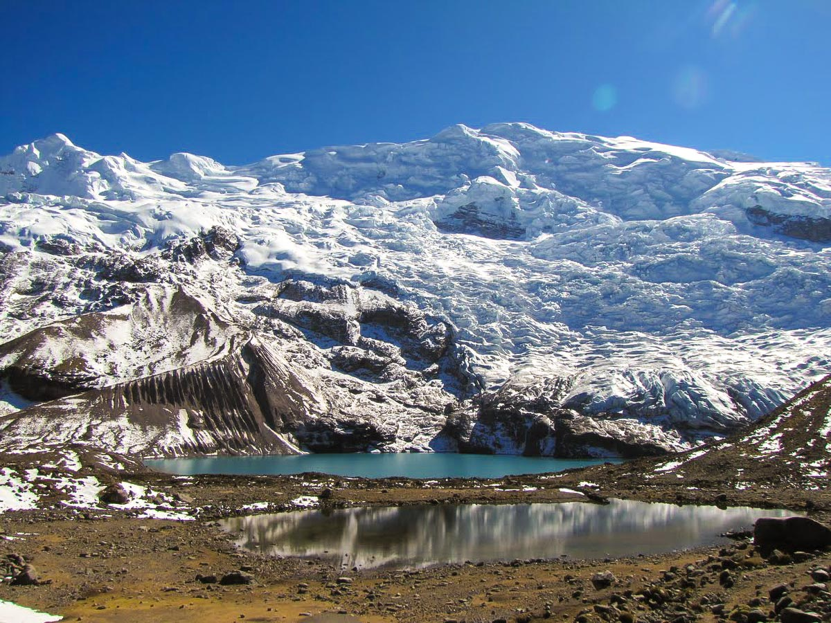 A small blue alpine lake under a snow-covered mountain in the sun