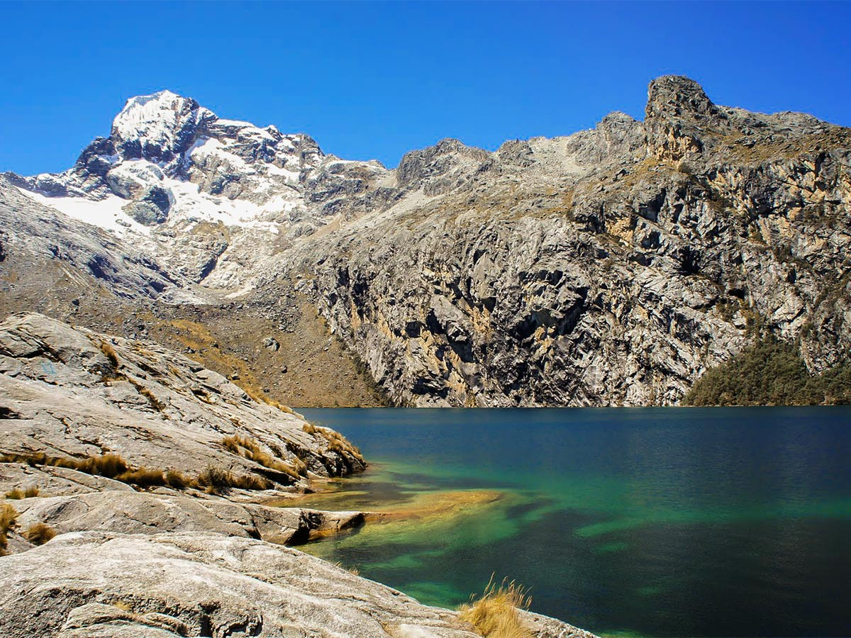 Low mountains and a blue alpine lake against blue sky