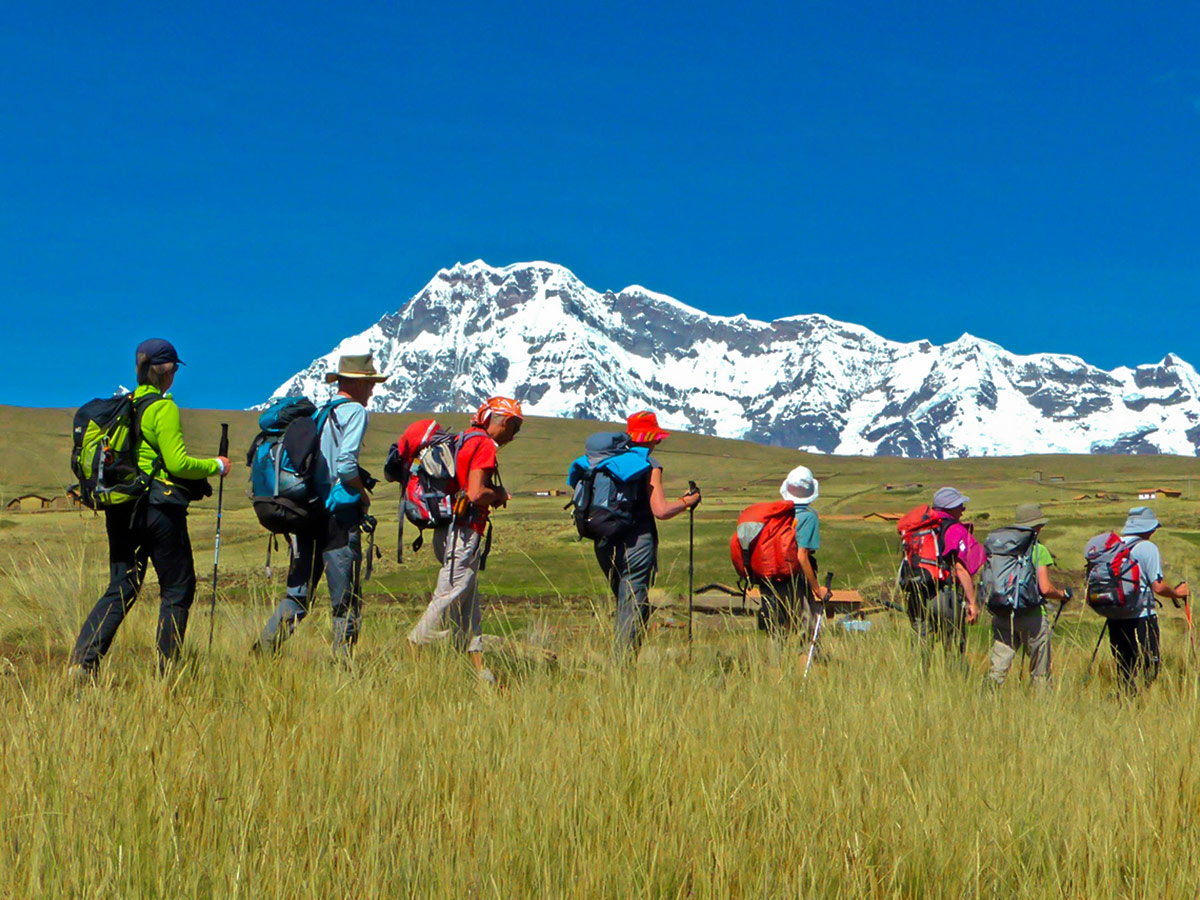 Eight people trekking through a field with mountains in the distance