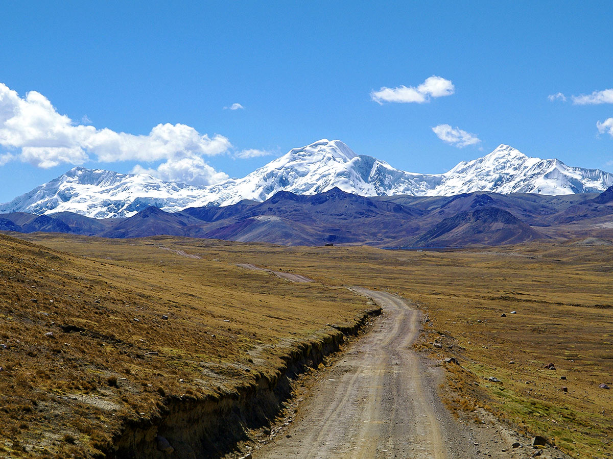 A dirt road cutting through an open plain with two layers of snow-covered mountains in the background