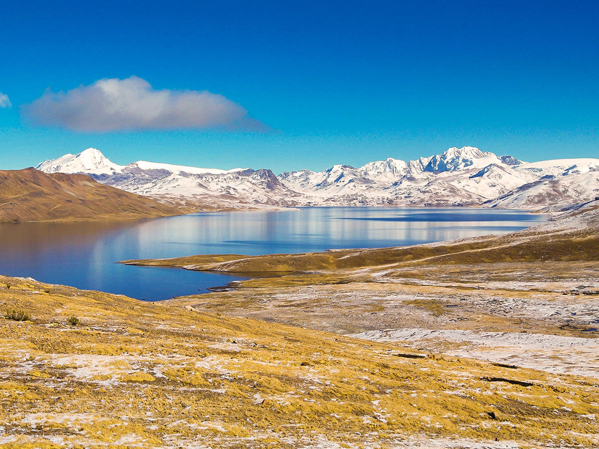 A calm blue lake surrounded by a smi-circle of low mountains covered in snow