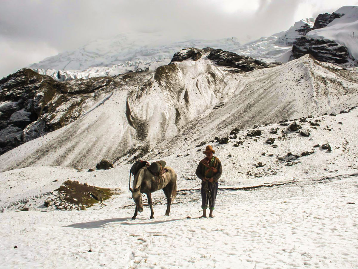 Traditionally-dressed man with a pack horse on a snow-covered mountain
