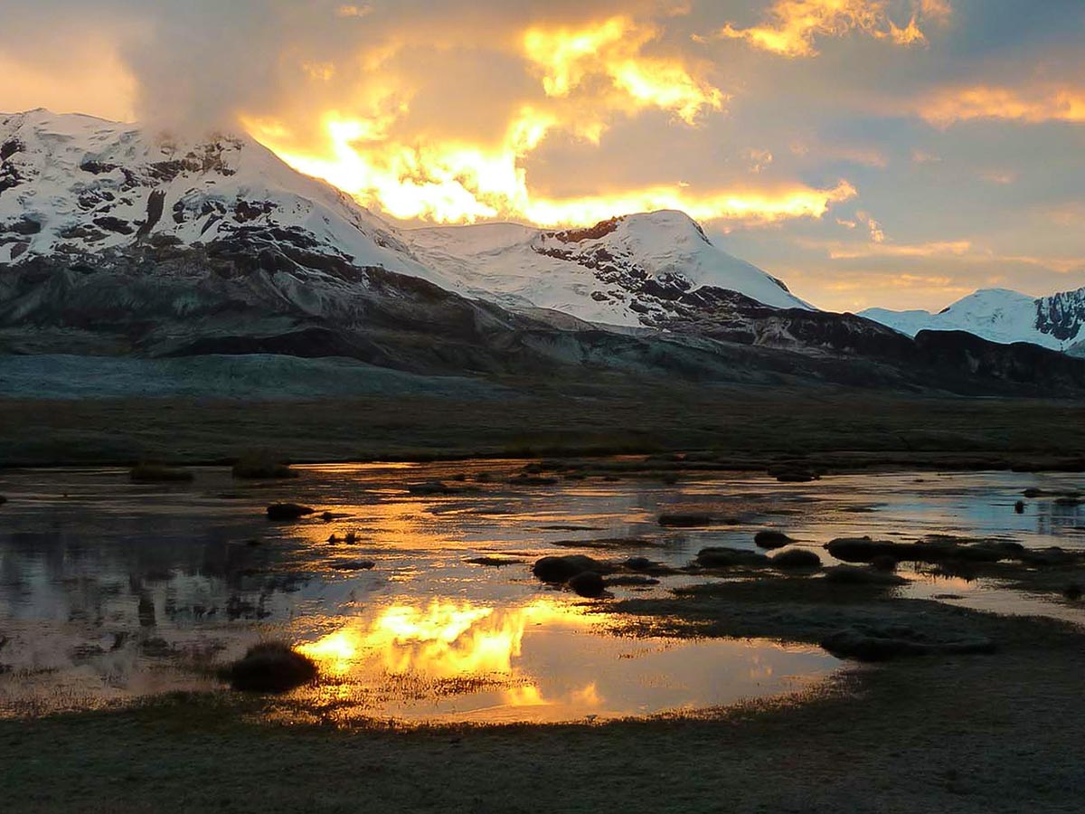 Sunset over snow-capped mountains reflecting in a large pond
