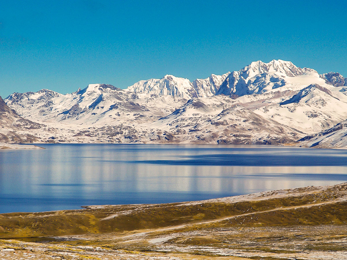 Wide blue lake with snow-covered mountains surrounding it