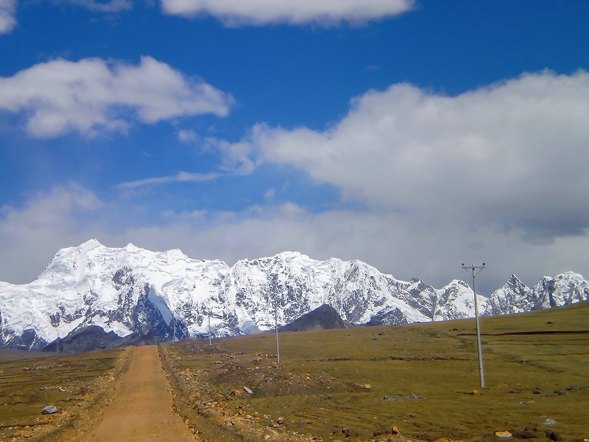 Dirt road heading towards snow covered mountains in the distance