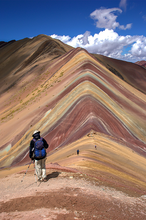 A person with a backpack and trekking poles walking along a striped, multicoloured ridge of rock in Peru